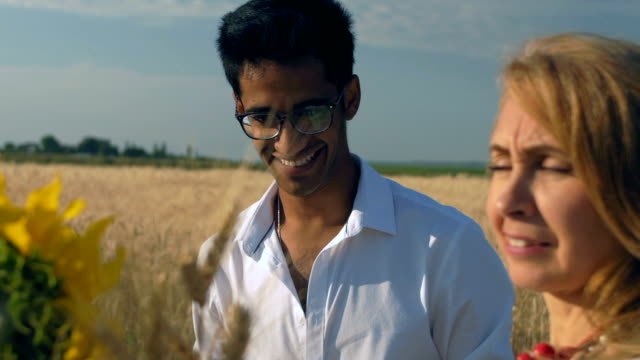 Close-up, Slow Motion, Indian Man in Glasses Smiling Being Near Adult Woman He Just Brought a Bouquet of Wheat Sprouts and Sunflower Close-up, Slow Motion, Indian Man in Glasses Smiling Being Next to the Adult Woman He Just Brought a Bouquet of Wheat and Wheat Sprouts Near the Wheat Field 天の川 stock videos & royalty-free footage