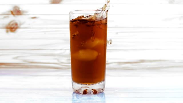 vídeos de stock, filmes e b-roll de closeup câmera lenta de chá gelado refrescante suco no copo com gelo cubos caindo com splash líquido na superfície reflexiva de madeira e madeira fundo - tea drinks