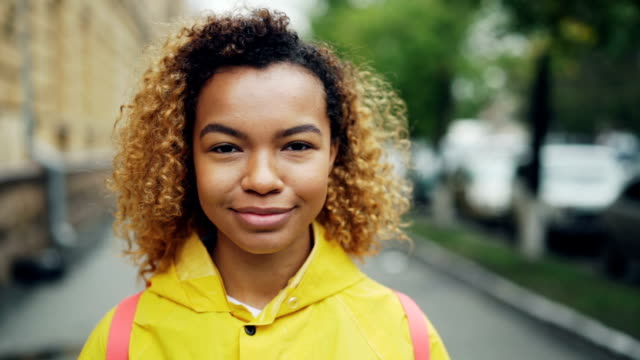Close-up slow motion portrait of attractive mixed race girl looking at camera with happy smile expressing positive emotions standing outdoors in the street.