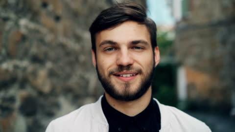 close-up slow-motion portrait gut aussehender bärtigen kerl in stilvoller kleidung draußen mit ernstem gesicht dann lächelnd und blick in die kamera. - junge männer stock-videos und b-roll-filmmaterial