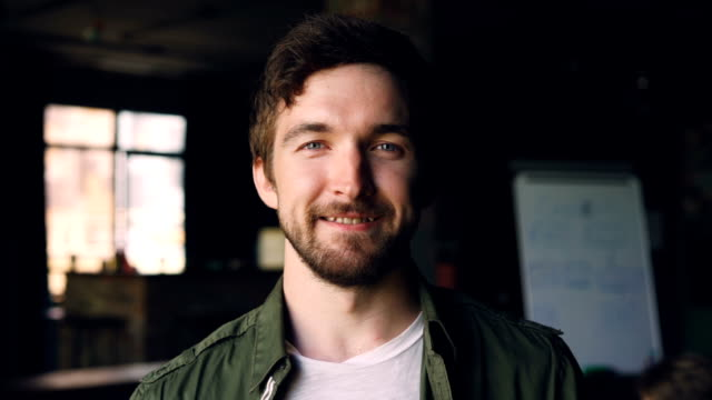 Close-up slow motion portrait of happy bearded guy with dark hair standing in modern office, looking at camera and smiling. People, work and career concept.