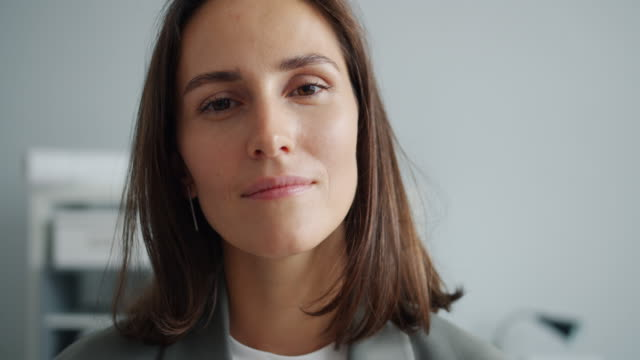 крупным планом медленное движение портрет молодой бизнес-леди смеется в офисе улыбается - близко к стоковые видео и кадры b-roll