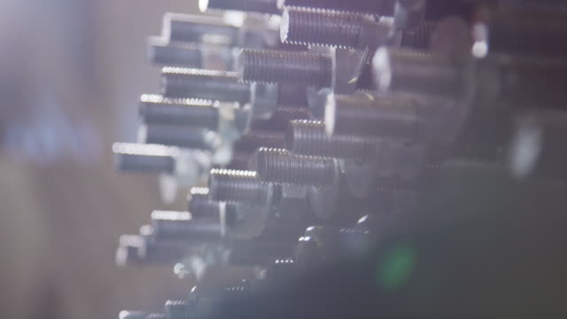 Close-Up Slow Motion Shot a Person Wearing Protective Work Gloves Screwing Nuts on to a Wall of Bolts (Manufacturing) Close-Up Slow Motion Shot a Person Wearing Protective Work Gloves Screwing Nuts on to a Wall of Bolts (Manufacturing) bolt fastener stock videos & royalty-free footage