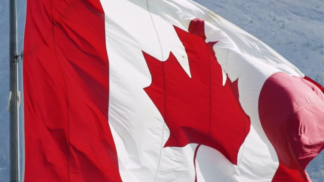 Close-Up, Slow Motion Shot of the Flag of Canada Blowing in the Wind with a Mountain in the Background on a Sunny Day