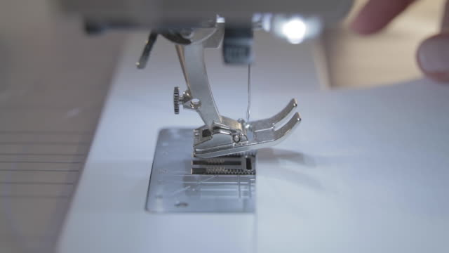 close-up slow motion video of work of the master seamstress and needle of the automatic sewing machine, good manicure - sarta video stock e b–roll