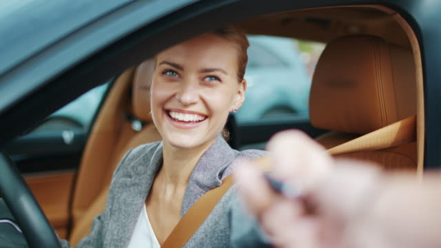 Closeup smiling woman sitting in new car. Happy woman getting keys from new car Closeup happy business woman taking new car keys at vehicle. Joyful executive woman getting keys from new car. Cheerful businesswoman sitting behind steering wheel at car. car key stock videos & royalty-free footage