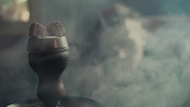 Close-up smouldering coals from the hookah in bowl in thick smoke in slow motion