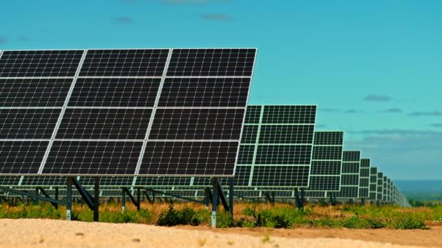vídeos de stock, filmes e b-roll de de perto, os painéis solares ficam com uma fileira ao ar livre. estação moderna para métodos inovadores de processamento de energia solar, usina de energia. 4k, prores - multicóptero
