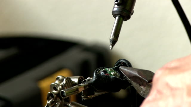 closeup soldering some ear buds video