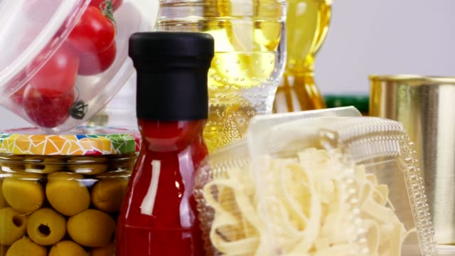 close-up, some nicely arranged groceries, food products rotate on white background. grocery online shopping. food delivery - vídeo