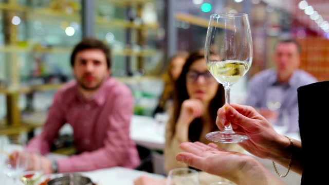Close-up - sommelier shakes the white wine in glass on degustation video