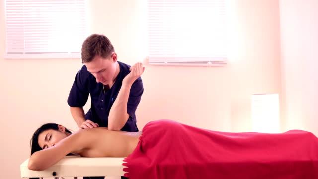 nahaufnahme spa-massage frauen schultern und rücken. männliche hände massagen zu einer frau in einem hellen raum - einzelne frau über 30 stock-videos und b-roll-filmmaterial