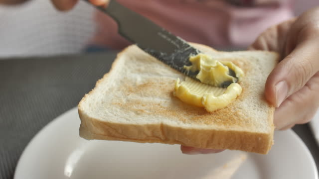 Close-up Spreading margarine onto bread