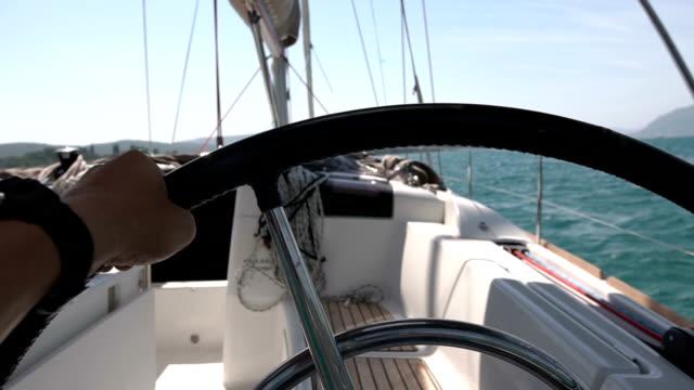 closeup steering wheel turning round. sailing boat with waves splashing - ster fragment pojazdu filmów i materiałów b-roll