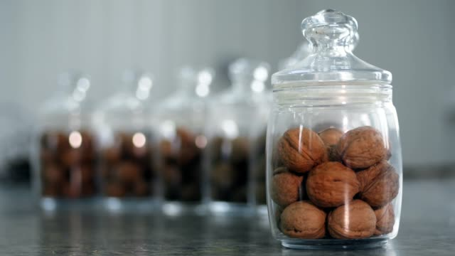 close-up, stored in glass jars are seeds, walnuts, various species grown on breeding, hybrids of nuts.
