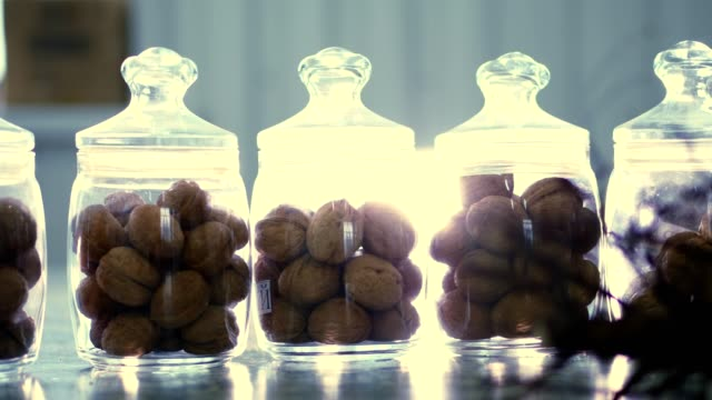 close-up, stored in glass jars are seeds, walnuts, various species grown on breeding
