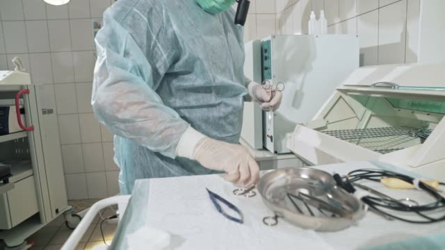 close-up, surgeon working in the hospital disinfects the medical instruments before the operation. doctor in glasses, professional clothes, a sterile mask and dressing gown. the concept of health, work in the clinic. surgical tools scalpel, clamp, tray at - lama oggetto creato dall'uomo video stock e b–roll