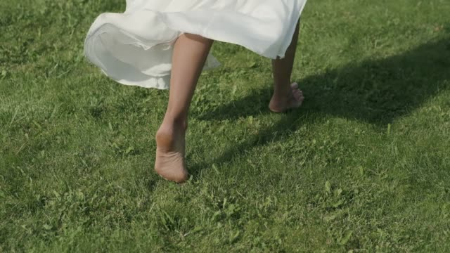 Closeup the bare feet of a girl who runs on the grass. Dress develops in the wind