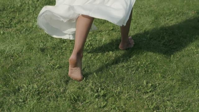 närbild de nakna fötterna på en tjej som springer på gräset. klänningen framkallar i linda - klänning bildbanksvideor och videomaterial från bakom kulisserna