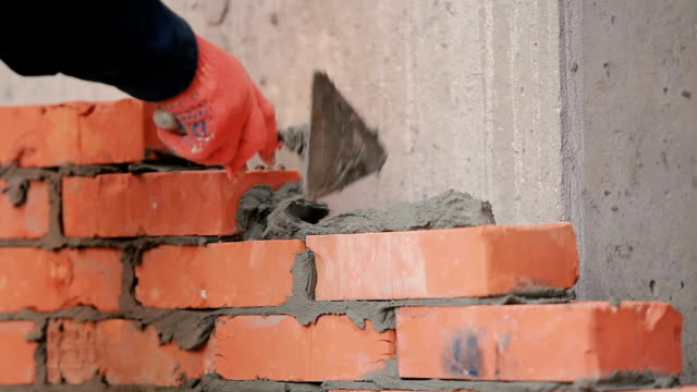 Close-up: the builder working with bricks