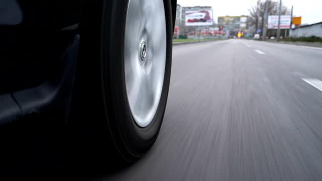 Close-up, The car wheel rotates along the asvaltated road.
