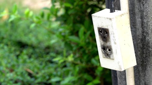 vidéos et rushes de agrandi la pendaison de prise électrique brancher et balançant sur béton électricité poster fond - vidéos de rallonge électrique