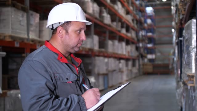 close-up. the face of a warehouse worker. a man makes notes in his folder. 4k slow mo - rozładowywać filmów i materiałów b-roll