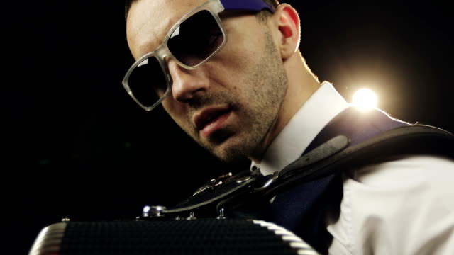 Close-up. The face of the musician in sunglasses on a bright back light. video