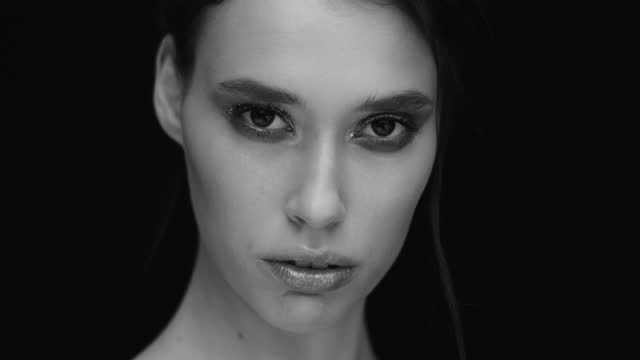 Close-up. The girl opens her eyes and looks at the camera. Black and white video. video