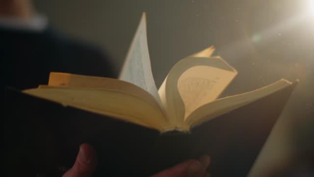stockvideo's en b-roll-footage met close-up, is de man snel flipping een oud boek en stof van het vliegt naar het licht. 4k - boekenkast