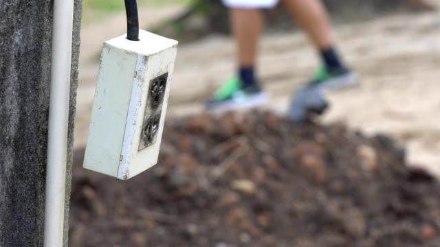 vidéos et rushes de agrandi le câble d'alimentation avec fiche suspendus et balançant sur fond de poteau béton électricité - vidéos de rallonge électrique