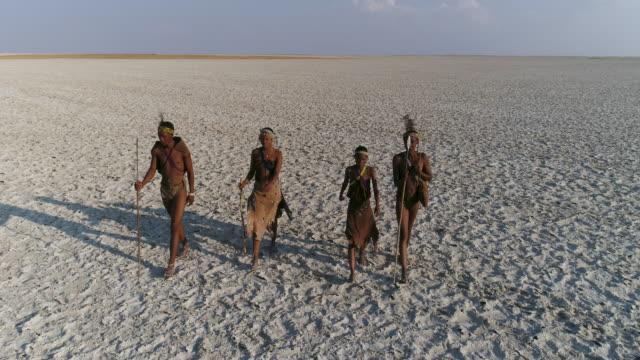 stockvideo's en b-roll-footage met close-up dan hoge uitzoomen luchtfoto van vier san bosjesmannen lopen over de enorme uitgestrektheid van de makgadikgadi pans, botswana - vier personen