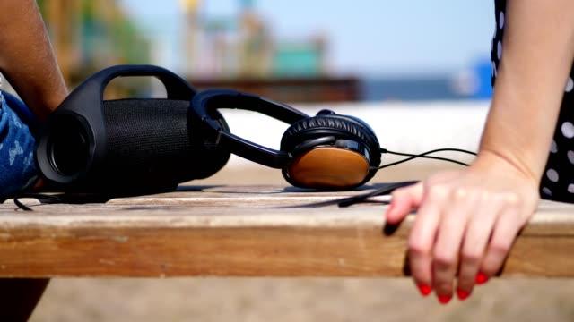 close-up, gibt es große kopfhörer und einen kleinen, mini musik bluetooth tragbaren schwarzen zylinder drahtlose lautsprecher auf der bank, im sommer am strand - redner stock-videos und b-roll-filmmaterial