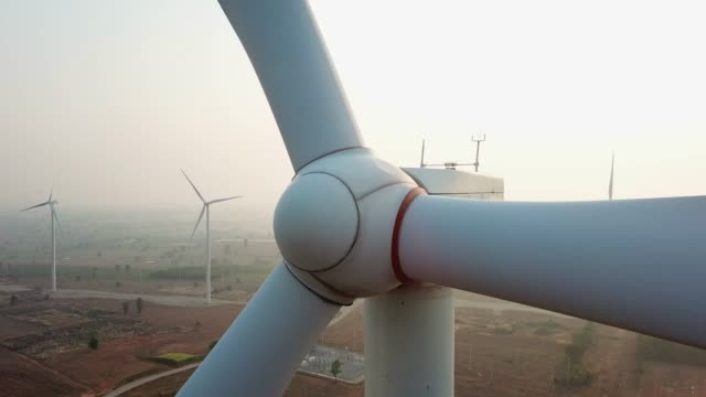 close-up to a windmill in wind turbines farm, zoom out - turbina a vento video stock e b–roll