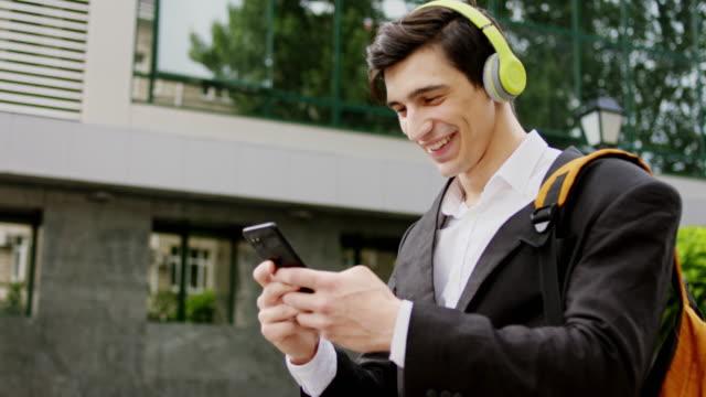 närbild till kameran karismatisk man i kostym med sin telefon för att skriva något när han gick på gatan han bär gröna hörlurar för att lyssna musik - blazer bildbanksvideor och videomaterial från bakom kulisserna