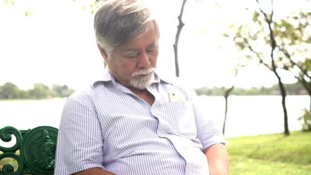 広い視野にクローズ アップ: 誰かを待っている間昼寝の祖父 - ベンチ点の映像素材/bロール