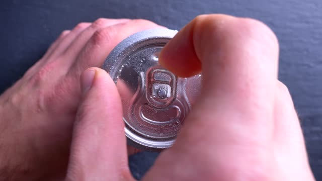 Closeup top bottom shoot of hand opening the can of energy drink