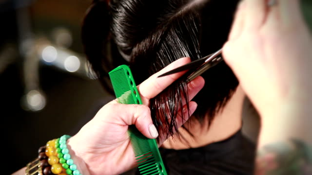 Closeup top view of stylist cutting a young woman's hair video