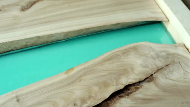 Close-up tracking left of unfinished handmade tabletop of wood and turquoise epoxy resin placed on workbench in joinery