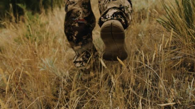 Closeup tracking shot of a hunter's feet as he walks through the wild grass.