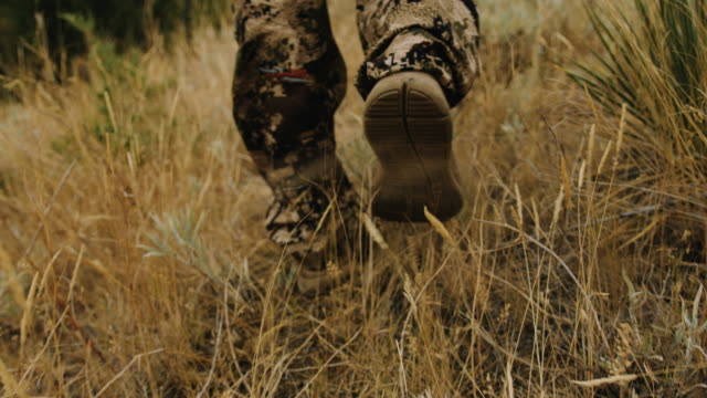 closeup tracking shot of a hunter's feet as he walks through the wild grass. - hunting stock videos and b-roll footage