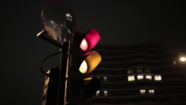 Close-Up Traffic Light At Night And Moving Vehicles
