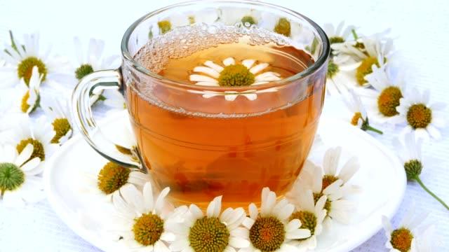 vídeos y material grabado en eventos de stock de primer plano, transparente, vaso con té de manzanilla, en un plato blanco. todo está decorado con flores de manzanilla - manzanilla