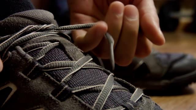 primo piano legando lacci delle scarpe da ginnastica. atleta legato lacci delle scarpe, scarpe da corsa. da vicino. rallentatore. - annodare video stock e b–roll