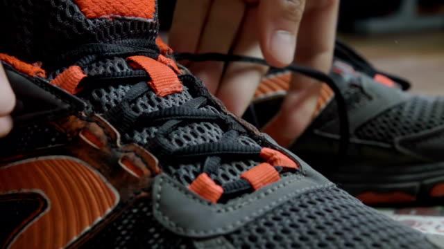 stockvideo's en b-roll-footage met closeup koppelverkoop schoenveters op sneakers. atleet vastgebonden schoenveters, loopschoenen. close-up. slow-motion. - running shoes