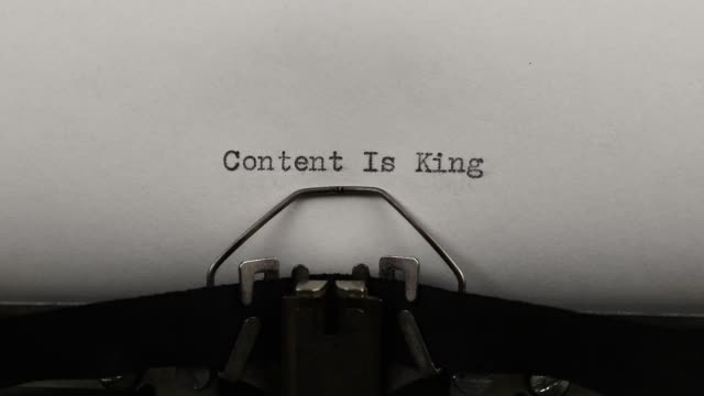 close-up typing a text content is king, old vintage typewriter with a sheet of paper