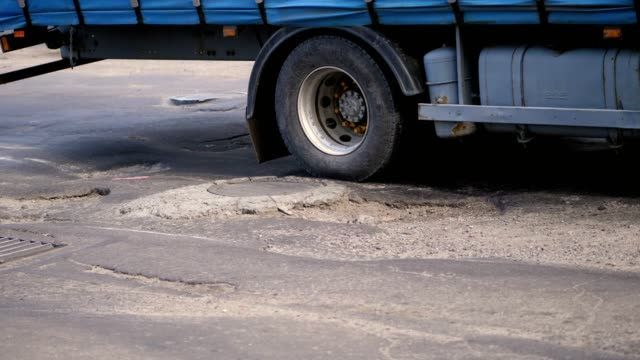 close-up, very poor road coverage, many pits, curved asphalt, a large truck slowly passes a stretch of road in disrepair. the road needs repair - водная яма стоковые видео и кадры b-roll
