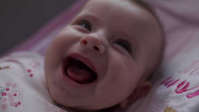 Close-up video of a little baby smiling and laughing