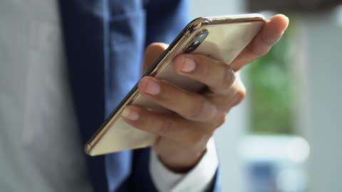 vídeos de stock, filmes e b-roll de vídeo close-up de mãos do homem de negócios na internet com telefone inteligente - smartphone