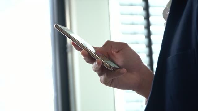 nahaufnahme video von geschäftsmann hände surfen im internet mit smartphone - online dating stock-videos und b-roll-filmmaterial